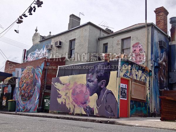 """这是面积较大的一副外墙人物手绘墙壁画,画面上的黑人小男孩正在吃着糖果,整幅手绘墙绘制逼真细致,可以看出绘制者的精良用心。墙体彩绘使得整个街道跟着活泼跃动起来。 大小手绘,您身边的墙绘壁画专家!更多墙体彩绘详情请点击>大小手绘墙绘创意(http://www.hwdaxiao.com) [[img ALT=""""高空墙绘 创意墙绘 外墙彩绘 人物手绘 文化墙壁画 北京墙绘公司 手绘墙 墙体彩绘 墙绘价格 手绘壁画"""" src=""""http://simg."""